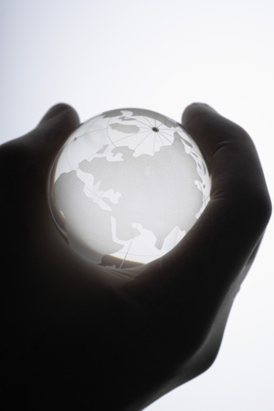 forensic science: Human hand with medical gloves gripping glass globe against white ,close up
