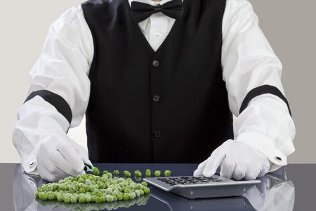 waistcoat: Man holding pea in tweezer while using calculator