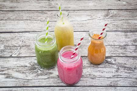 berry smoothie: Various colorful fruit smoothies in glass bottles Stock Photo