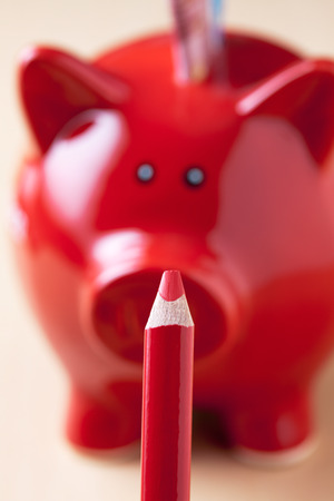 red pencil: red piggy bank and red pencil, close up, depth of field
