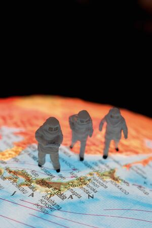 environmental damage: Close up of miniature figurines of astronomers on globe against black