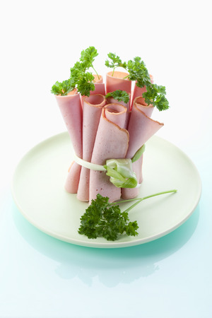 leberkaese: Close up of Leberkaese slices rolled up,tied and garnished with parsley on white