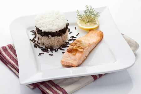 garnished: Salmon and rice tart garnished with dill,lemon slice,garlic in plate Stock Photo