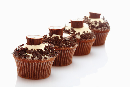 chocolate background: Close up of buttercream cupcake with chocolate crumble and chocolate candy against white background