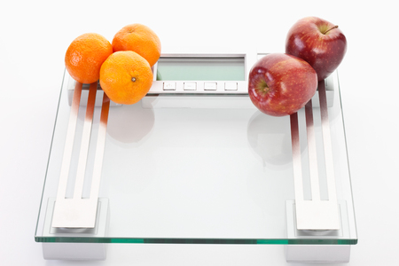 clementines: Apples and clementines on scales,close up Stock Photo