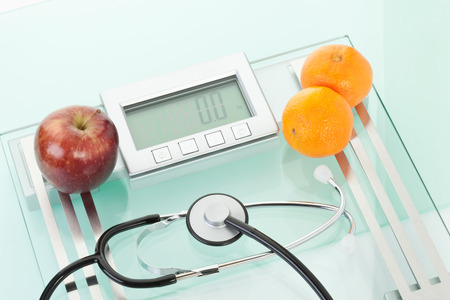 clementines: Apple,clementines with sethoscope on scales