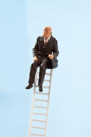 oldage: Businessman figurine sitting on ladder Stock Photo