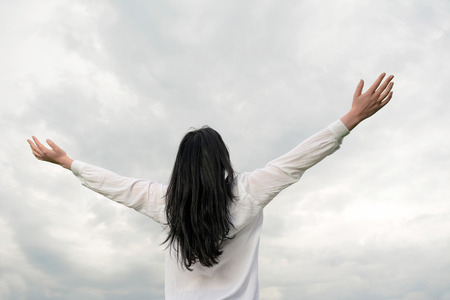 stretched out: Young woman and clouds, arms stretched out Stock Photo