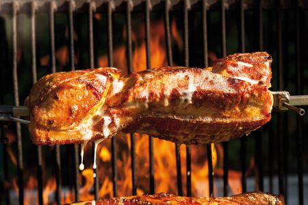 crackling: Pork roast with crackling roasting on charcoal grill