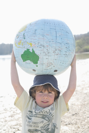 holding aloft: Germany,Bavaria,Ammer Lake,Close up of boy holding earth beach ball