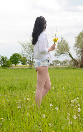 hot pants: Young woman with dandelions on meadow Stock Photo
