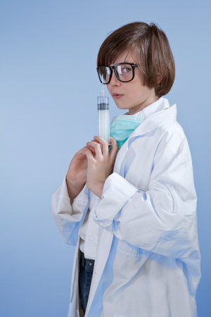 surgical coat: boy dressed as doctor and holding a medical injection,portrait