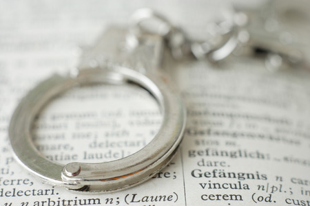 delinquency: Extreme close up of handcuffs on dictionary Stock Photo
