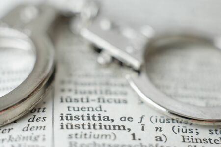 lexicon: Extreme close up of handcuffs on dictionary Stock Photo