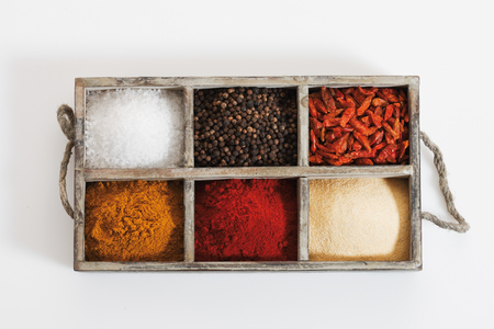 herbs boxes: Variety of spices and herbs in wooden box on white background