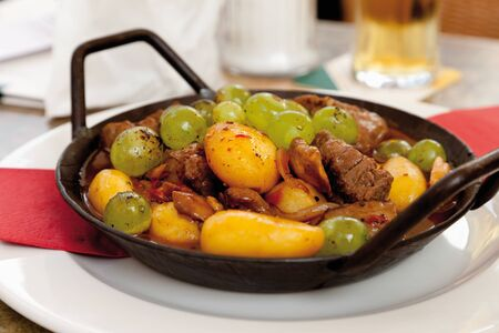goulash: Goulash with salt potatoes and grapes in pan Stock Photo
