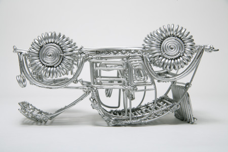 pliable: Upside down toy car made of pliable wire against white background,close up