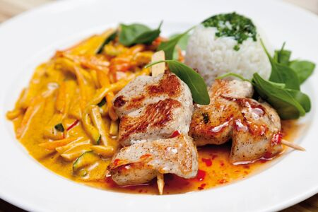 turkey hen: Close up of barbecued turkey hen spit with Madras-curry wok vegetables and boiled rice