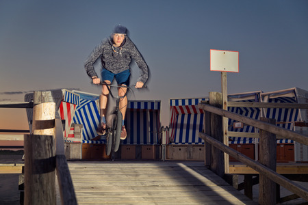 bmx bike: Young man jumping with his BMX bike on wooden ramp Stock Photo