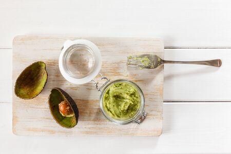 chopping board: Avocado cream, preserving jar on chopping board