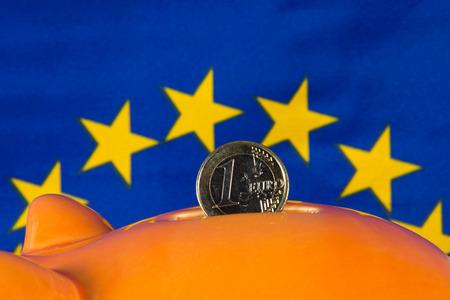 eu flag: Piggy bank with one euro coin, EU flag in background Stock Photo