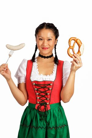 veal sausage: Asian woman wearing Dirndl holding pretze and veal sausage Stock Photo