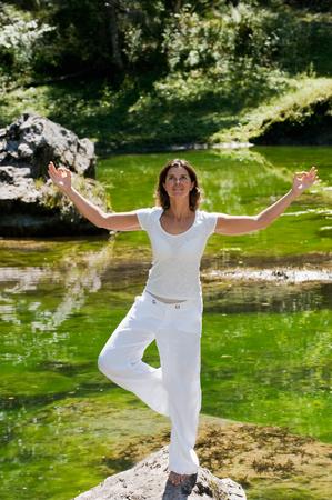 tree position: Austria,Salzburg,Mid adult woman meditating on a stone near gosau