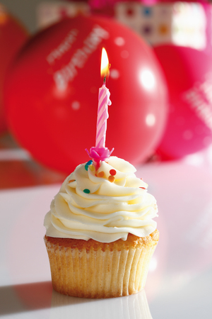 hundreds and thousands: Close up of vanilla buttercream cupcake with birthday candle