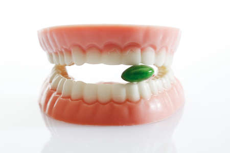 dental prophylaxis: Dentures made of sugar and white chocolate with tablet on white background,close up