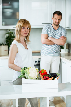 sceptic: Woman with vegetable box in kitchen, man looking sceptical