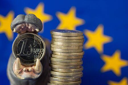 bacon bits: Euro coin in mouth of hippo figurine, EU flag