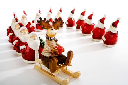 clauses: Santa Clauses queuing at sledge with elk Stock Photo