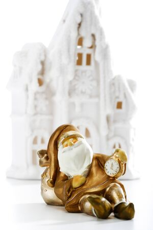 winter  house: Golden Santa Claus holding watch in front of winter house Stock Photo
