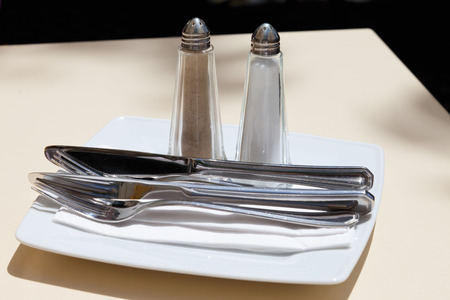 things that go together: Close up of cutlery with salt and pepper pots Stock Photo