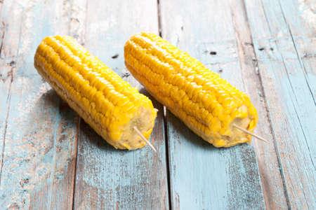 elote: Cierre de la mazorca de maíz ensartada en mesa de madera
