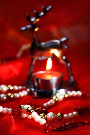 tea light: Christmas decoration with burning tea light and beads on red