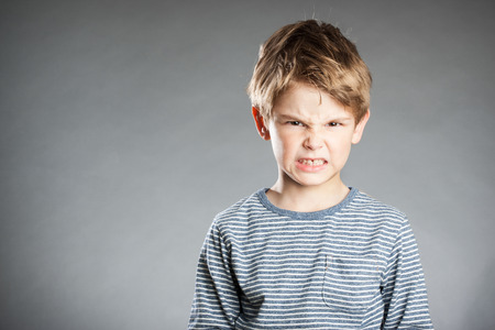 defiance: Portrait of boy, emotion, angry, grey background