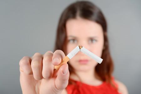 breaking: Young woman breaking cigarette