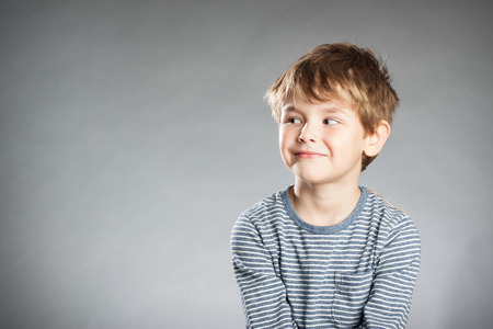 inquisitively: Portrait of boy, emotion, curious,  grey background