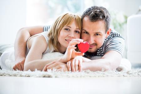 Glückliche liebevolle Paare, Herz-Box in der Hand