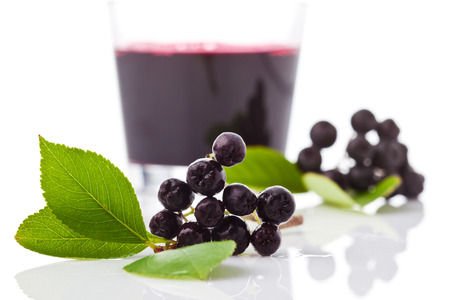 Chokeberries, Glass with aronia juice Stock Photo