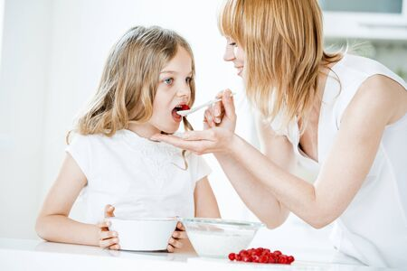 feed: Mother feeding daughter with muesli and raspberries