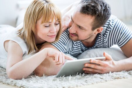 surfing the net: Couple with tablet lying on floor and surfing the net