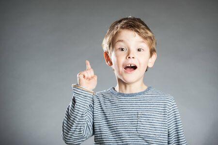 inventive: Portrait of boy, emotion, gesture, idea, grey background
