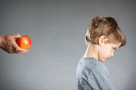 refused: Retrato de ni�o, la mano con la manzana, se neg�, fondo gris Foto de archivo