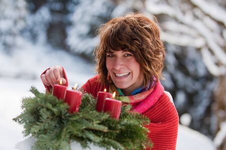 igniting: Austria,Salzburg Country,Flachau,Close up of young woman igniting candles of advent wreath in winter