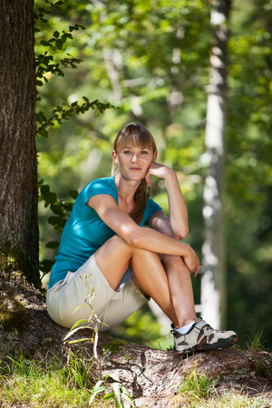fringes: Germany,Upper Bavaria,Young woman resting under tree,smiling,portrait