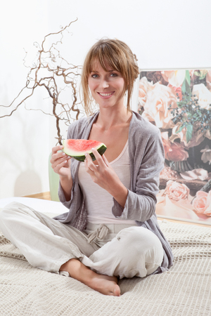 fringes: Young woman sitting on bed and holding watermelon slice in morning,smiling