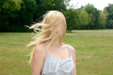 unkempt: Young woman with unkempt hair in park Stock Photo