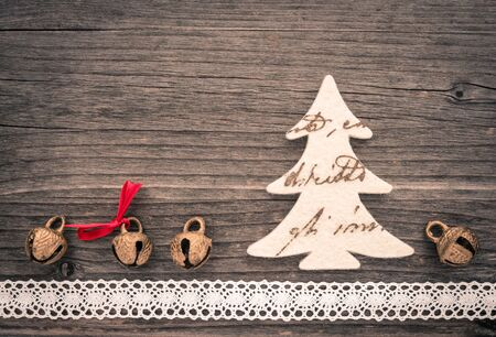 christmastime: Christmas decoration of felt, christmas tree, bells and lace on wood Stock Photo